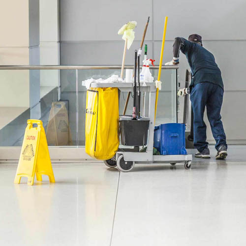 commercial cleaner cleaning glass panels under railing with yellow cleaning sign at left of picture and cleaning cart with mop and supplies in the centre