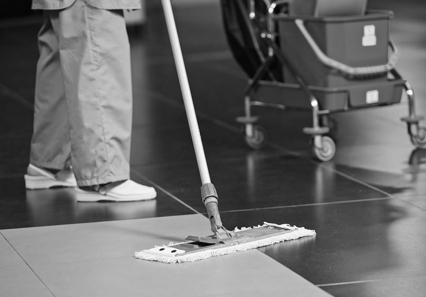 Black and white commercial floor duster being used by LCS cleaner