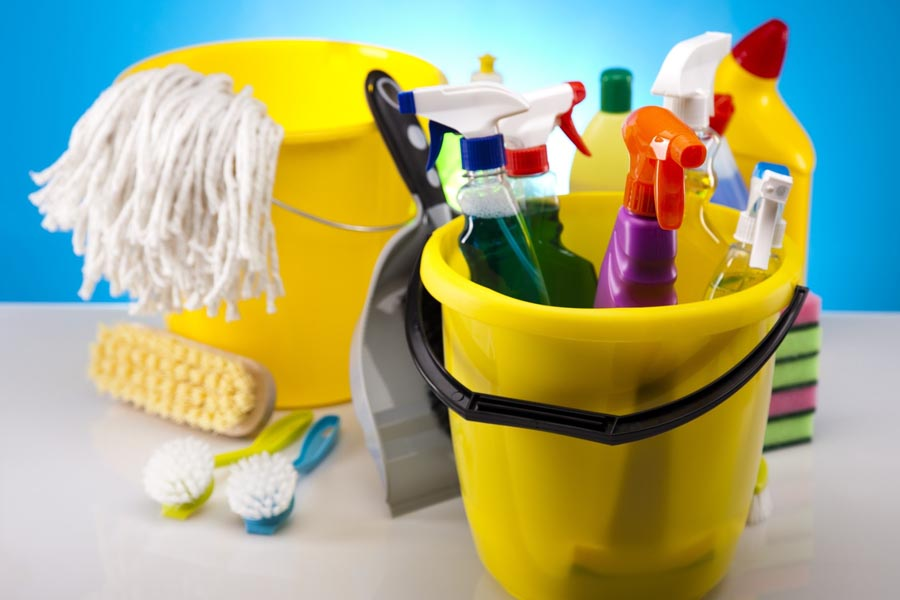 Janitorial Cleaning Supplies in yellow buckets with dustpan and brush, a mop head and cleaning chemicals