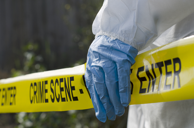 yellow crime scene tape held by a blue gloves hand for crime scene cleaning image