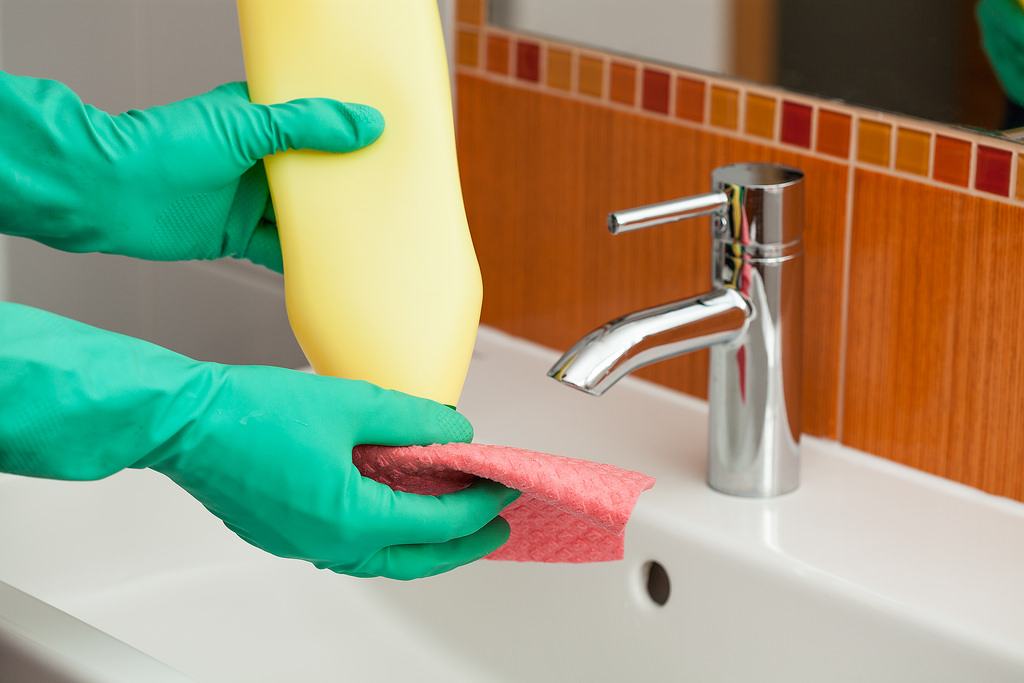 man cleaning with green-blue gloves on, cream cleaner and cloth about to clean sink