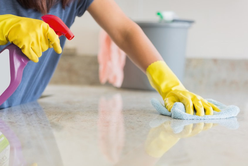 woman cleaning countertop with cleaning solution and yellow marigolds
