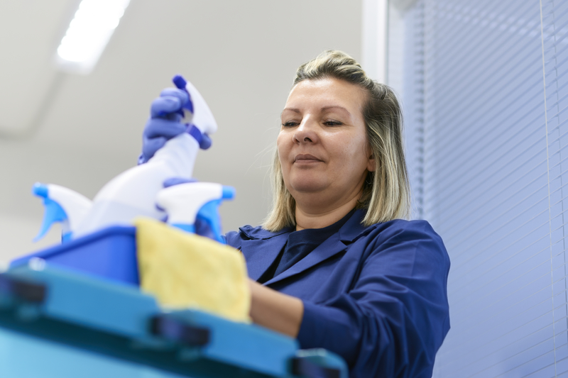 Women at work, portrait of happy professional female cleaner arranging bottles of detergents on trolley in office