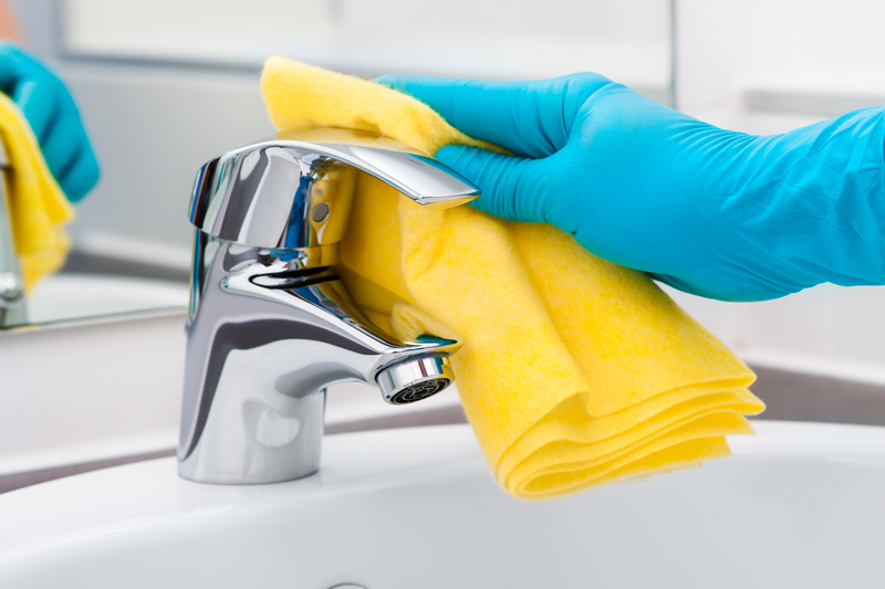 cleaning the bathroom tap with blue gloves and yellow cloth